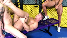One guy jerks his meat as he watches two more fucking in the gym