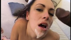 Horny brunette fucks two black cocks and takes their load in her mouth