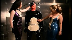 Mistresses dress up their slave in latex getting ready to torture her