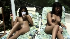 Two astonishing Asian babes lie side by side and expose their bodies