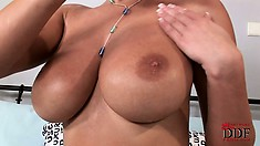 Covering her fabulous tits with oil, the hot blonde makes them look even more amazing