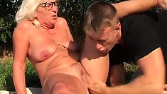Naughty blonde granny gets fucked deep by a young stud in the outdoors